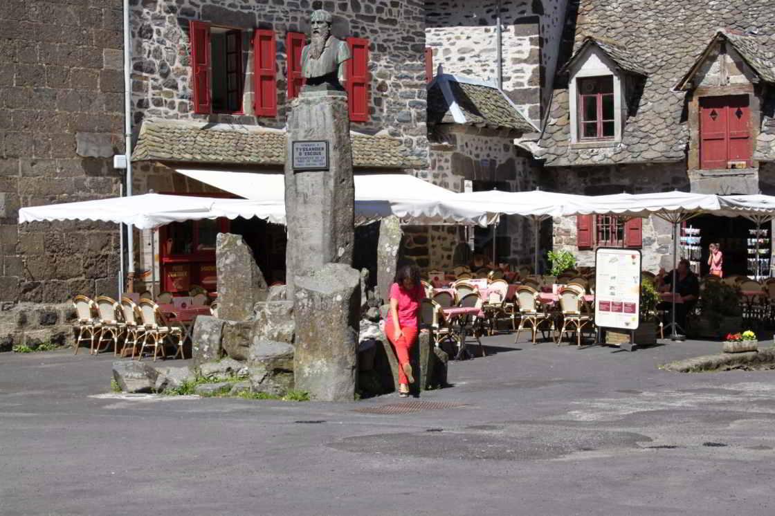 vrouw zit voor een terras in de plaats Salers in Frankrijk
