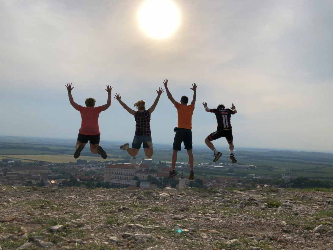 Vier mensen springen omhoog op de Heilige Berg in Mikulov