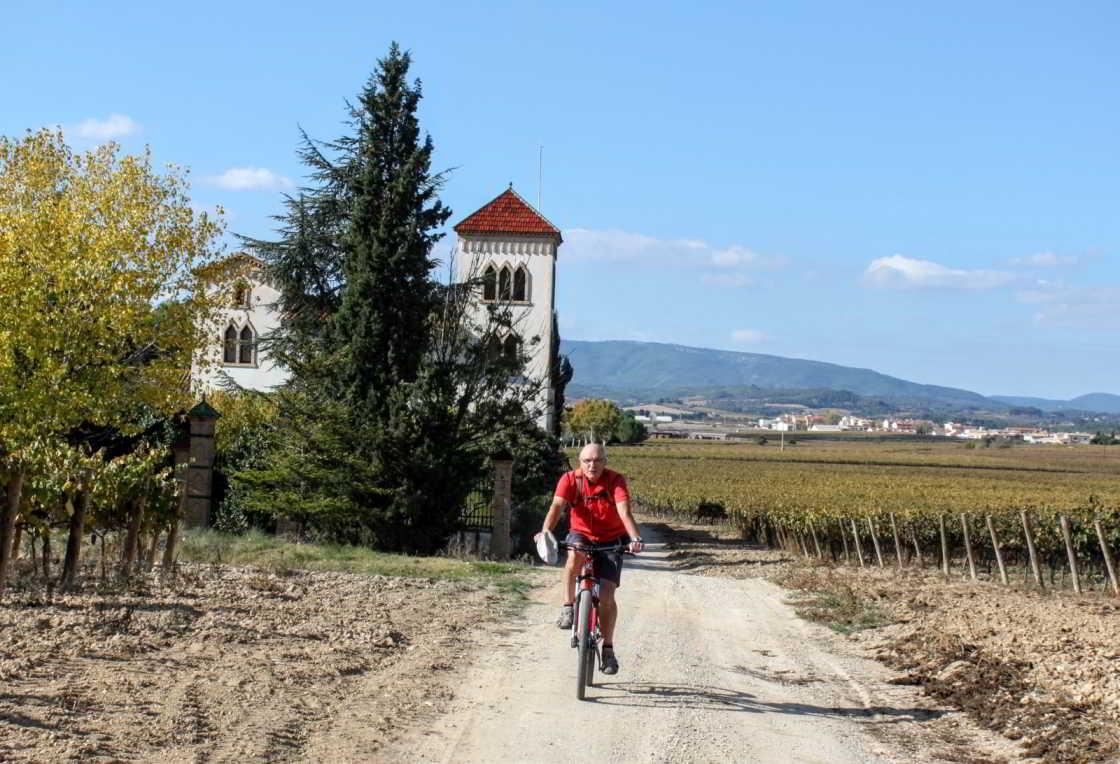 fietser met huis op achtergrond in Penedès