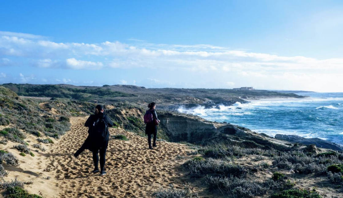 twee vrouwen wandelen langs de kustlijn van Alentejo
