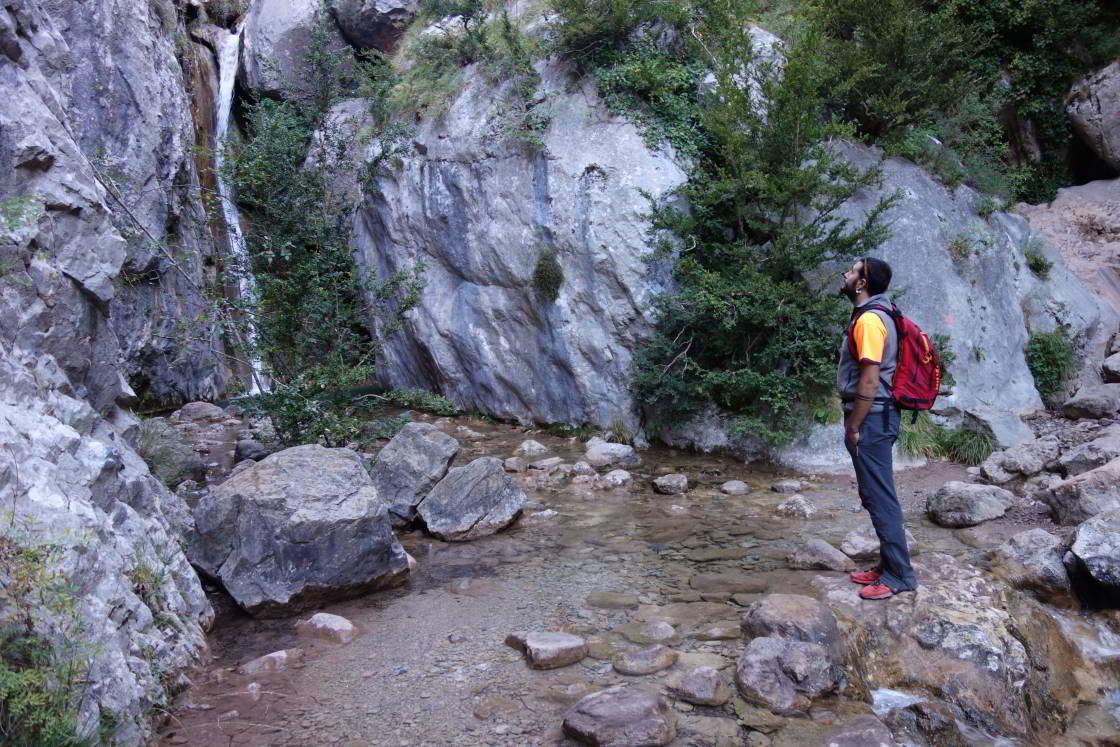 man staat bij watervalletje